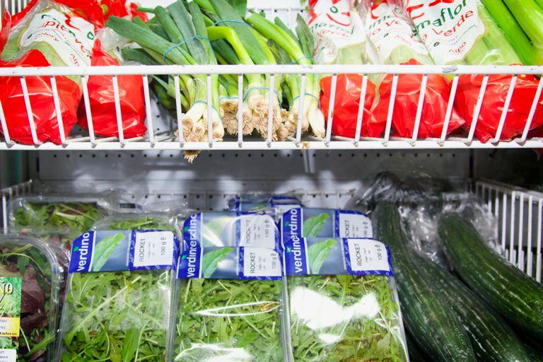 Leafy greens presented on supermarket produce shelving