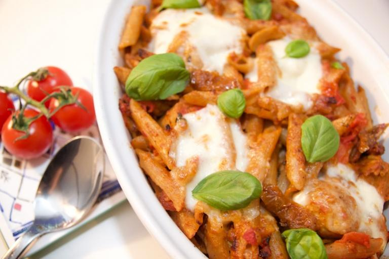 Cheesy pasta dish with vegetarian sausages and topped with mozzarella cheese and basil